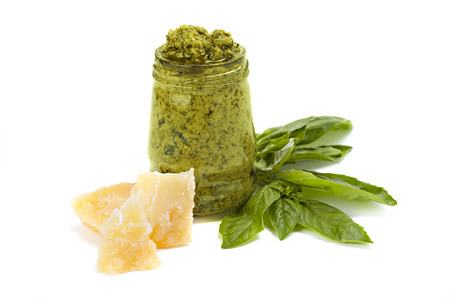 Green pesto in the glass with piece of cheese and leaf of basil isolated on white. Imagens