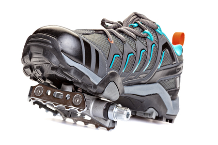 clasp feet: Closeup of cycling shoes with pedal attached to the sole  isolated on  white background.