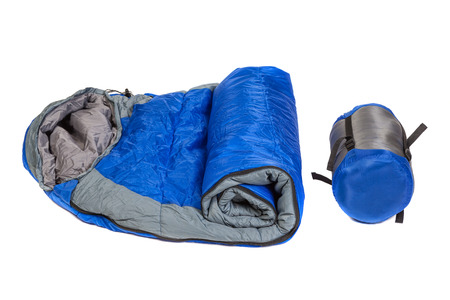 tightness: Two of  the same sleeping bags in a compression bags and unpacked  isolated on white background. Studio shot. Stock Photo