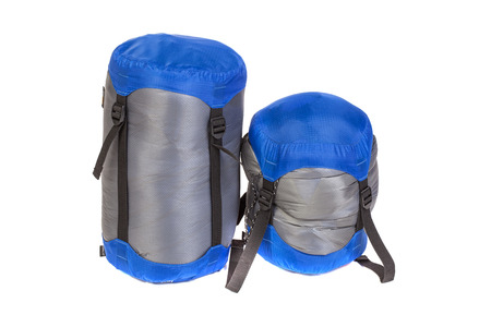 tightness: Tourist sleeping bags  packed with varying degrees of compression isolated on white background. Studio shot.