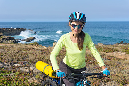 Adult attractive female cyclist standing on a ocean coast and looking at the camera. Imagens