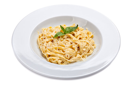 grated parmesan cheese: Plate of a italian pasta with grated parmesan cheese and basil leaf.
