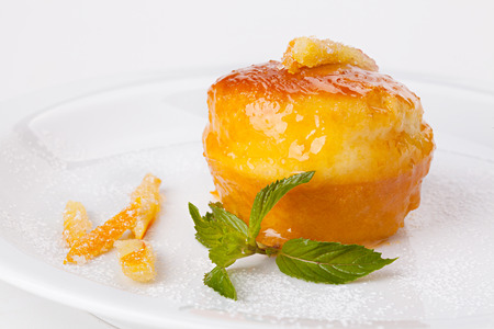 Italian sweet Baba of Naples with candied fruit and mint leaves. Stock Photo