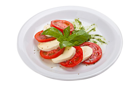 Caprese salad with ripe tomatoes and mozzarella cheese with fresh basil leaves  isolated on the white background. Studio shot. Top view.