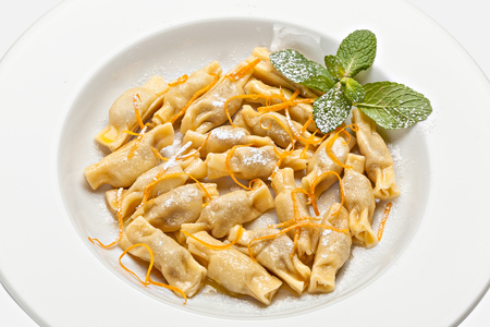 Close-up of the plate of ravioli with grated orange peel and a mint leaf. Top view. Stock Photo