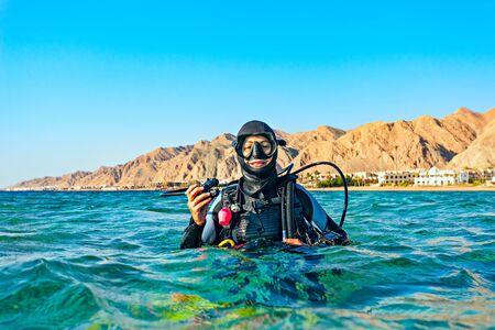 La mujer buceadora flotó en la superficie del mar y sonríe. Mar Rojo, Egipto. Foto de archivo
