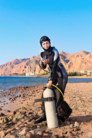 Buzo femenino comprobando su equipo en la costa antes de bucear. Egipto, Dahab, Mar Rojo. Mirando a la cámara.