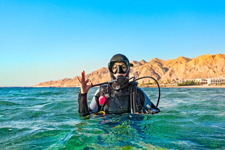 Woman diver floated on the surface of the sea and shows a hand sign that all is well. Red Sea, Egypt. Foto de archivo