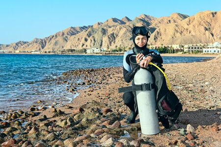 Female diver checking her equipment on the coast before diving. Egypt, Dahab, Red Sea. Looking At Camera.