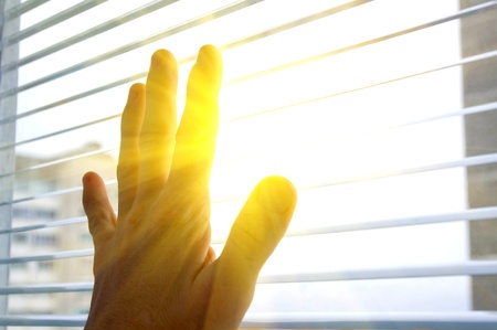 jalousie: The human hand touches to window