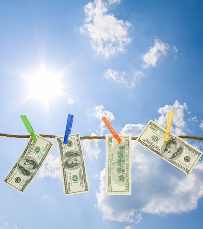 Dollars on a rope isolated on blue sky background.