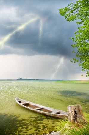 Boat at coast against a coming nearer thunder-storm Stock Photo - 11603381