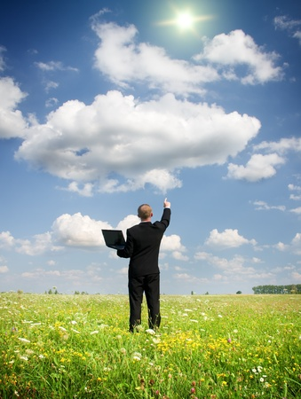 businessman from notebook on summer meadow photo