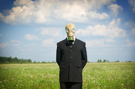 man in gas-mask on meadow.Conceptual composition. photo