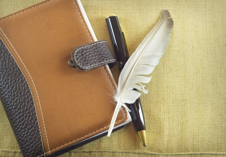 Elegant feather over a notebook photo