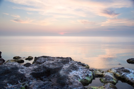 Sea and rock at the sunset. Nature composition. Stock Photo