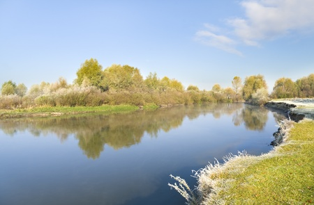 Coast of the autumn river covered with hoarfrost photo
