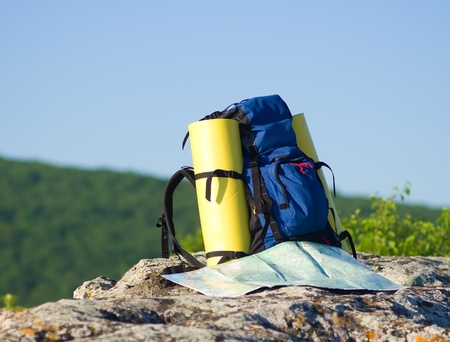 Backpack and map in mountain.nature composition. Standard-Bild