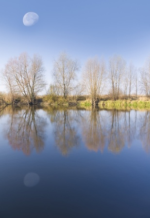 Coast of the autumn river reflected in its waters photo