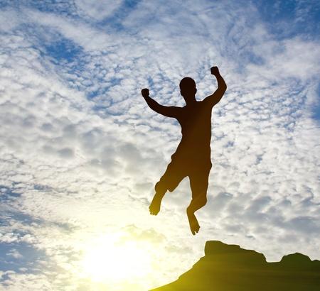 silhouette of jumping man on sunrise photo