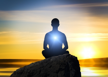 Silhouette of the meditating person against a fired background photo