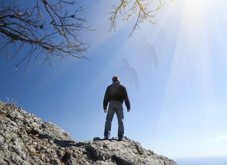 astral body: el hombre sobre la roca en la de Presencia espiritual. Foto de archivo