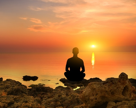 Silhouette of the meditating person against a sea decline Stock Photo - 12625696