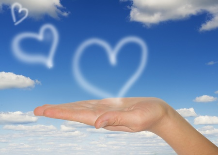 white hearts  in woman's hand on blue background