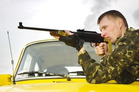 gorra policía: Francotirador en camuflaje en el coche al atardecer al aire libre.