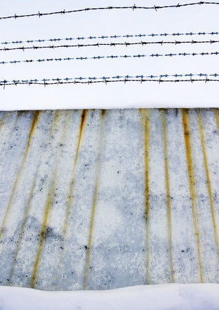 Concrete protection with a barbed wire covered with snow Stock Photo - 12625623