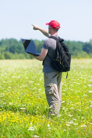 THE YOUNG MAN WITH THE LAPTOP ON A FLOWER MEADOW photo