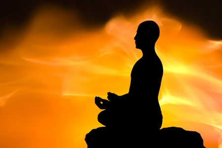 Silhouette of the meditating person against a fired background Stock Photo - 12625906