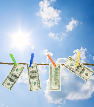 money laundering: Dollars on a rope isolated on blue sky background