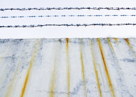 Concrete protection with a barbed wire covered with snow Stock Photo - 13264238