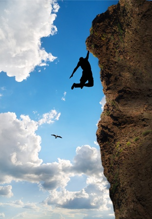 rock climber climbs the steep cliff to the top against the blue sky Stock Photo