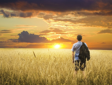 man in wheat field joying sunset photo