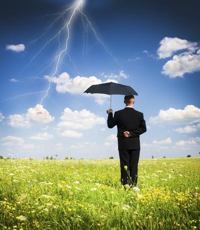 A businessman holding an umbrella in a storm  Stok Fotoğraf