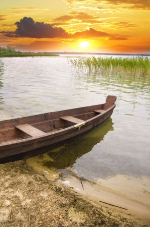 Boat at coast against a sunset. Nature composition. Stock Photo - 14823394