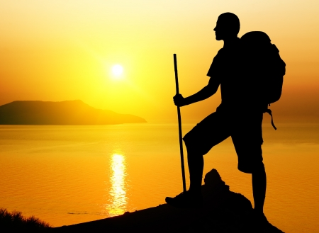 Silhouette of the tourist on sundown background  Sport and active life photo