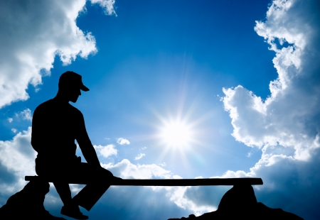 bench alone: The person sits on a bench against the sky