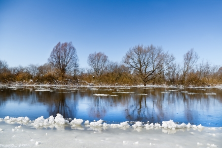 Ice floes floating on winter small river under the blue sky photo
