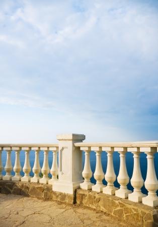 Kind on ocean from a stone balcony photo