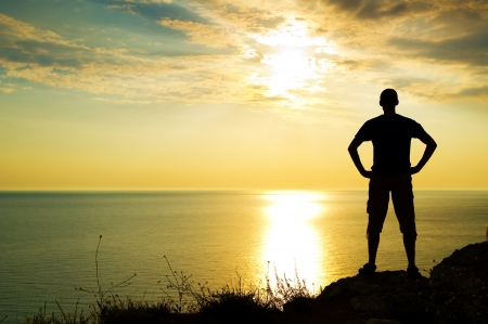 filed: silhouette of man on the sunset on rock Stock Photo