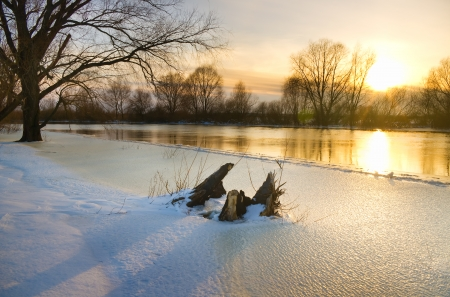 Sunset over frozen river in winter photo