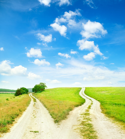 dirt road: Cross roads horizon with grass and blue sky