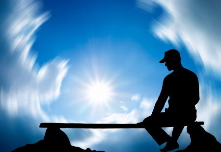 The person sits on a bench against the sky