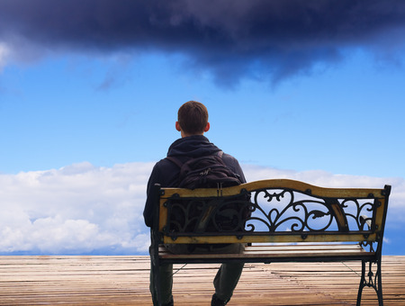 outdoor bench: The lonely man sits on a decline.Creative Outdoor Photo.