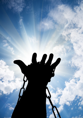Hands tied up with chains against blue sky Stock Photo - 31571165