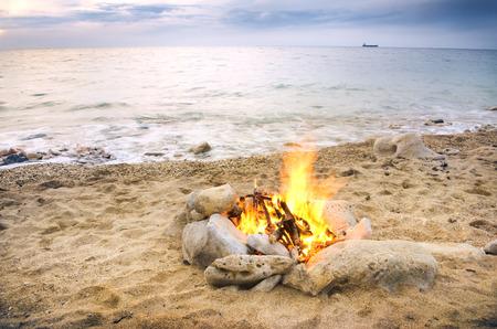 Lonely night fire on seacoast in the autumn Standard-Bild