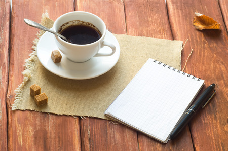 Cup of coffee and sugar on wooden table and open notebook photo